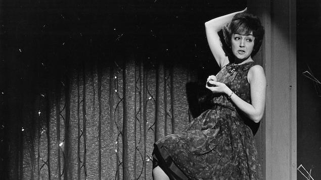 La chanteuse Lucille Dumont, assisse sur un tabouret, une pomme à la main, chante une chanson.