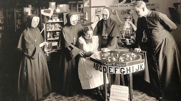 Photo en noir et blanc montrant une jeune fille entourée de trois religieuses et d'un abbé, devant un plateau affichant des lettres de l'alphabet.