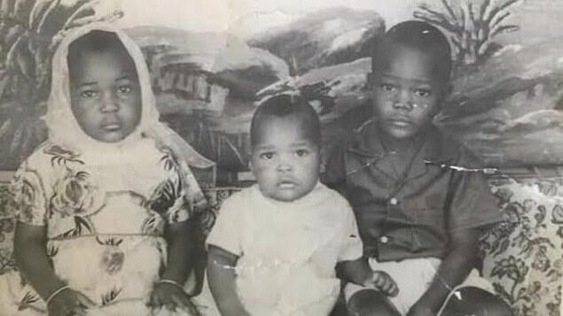 Trois jeunes enfants sur une photo d'époque.