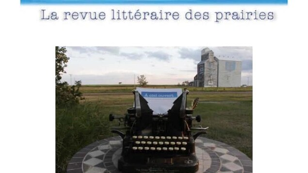 Au premier plan, une ancienne machine dactylo sur une table avec une page vierge qui affiche l'entête À ciel ouvert, En arrière plan, un champ des Prairies, et un silo à grain.