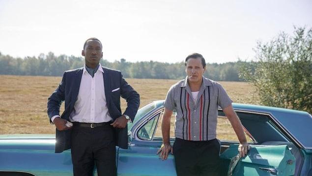 Les deux hommes sont devant une voiture bleue.
