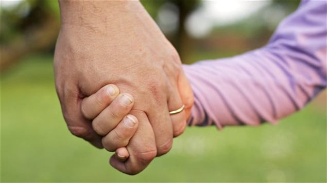 Un adulte tient la main d'un enfant.