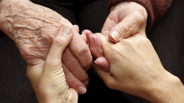 Gros plan sur une personne âgée qui tient les mains d'une personne plus jeune.