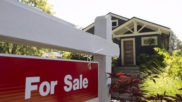 Une pancarte « À vendre », en anglais, en avant-plan de l'image devant une maison.