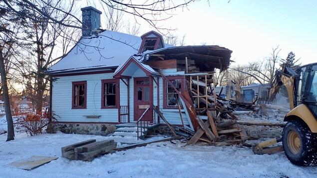 Une maison ancienne en train de se faire démolir par une pelle mécanique.