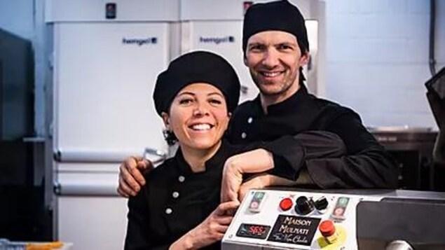 un couple en tenue de travail dans leur usine de chocolaterie.