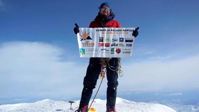 Jean-François Dupras, habillé en alpiniste, est au sommet d'une montagne. Il tient une banderole où est écrit Vaincre la maladie mentale un sommet à la fois.