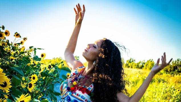 Une femme danse au soleil près d'un chant de tournesols.