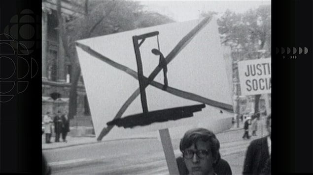 Image en noir et blanc d'un homme tenant une pancarte sur laquelle on voit le dessin d'un bonhomme pendu
