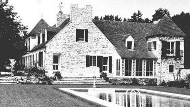 Photo d'archives d'une grande maison d'époque luxueuse avec une piscine creusée.