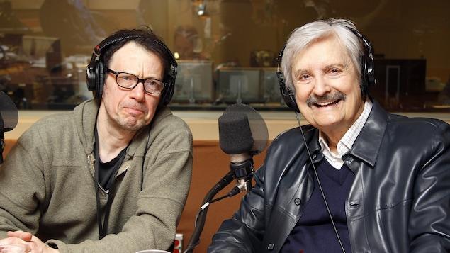 Le réalisateur Manuel Foglia et le journaliste Marc Laurendeau posant devant leurs micros dans le studio 18 de Radio-Canada