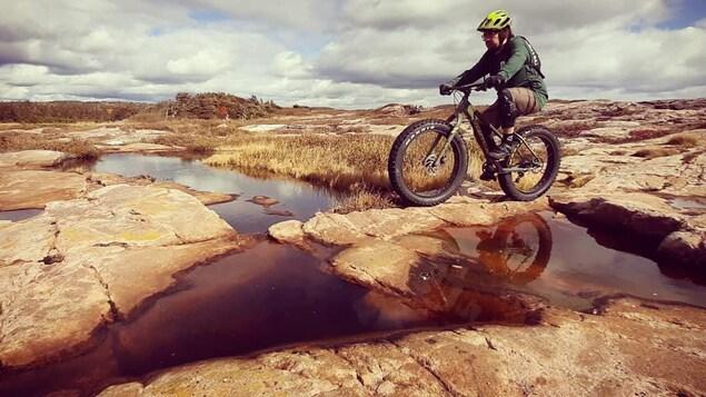 Le journaliste Marc-Antoine Mageau sur son fatbike, à la rivière Pigou, sur des rochers, sur la Côte-Nord.