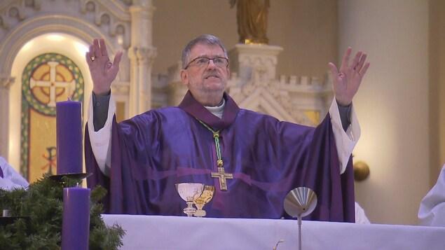 Un homme d'Église en habit mauve devant l'autel.