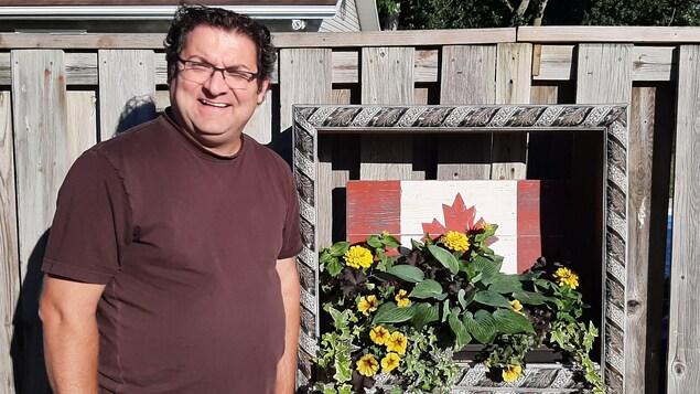 Mark Couture dehors devant son drapeau du canada qu'il a conffectionné lui même