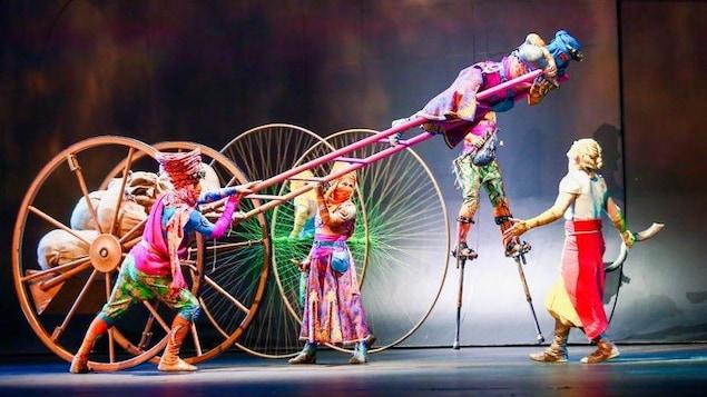 Des artistes de cirque font des acrobaties sur une grosse charrette avec d'énormes roues alors que d'autres se promènent en échasses sur scène.