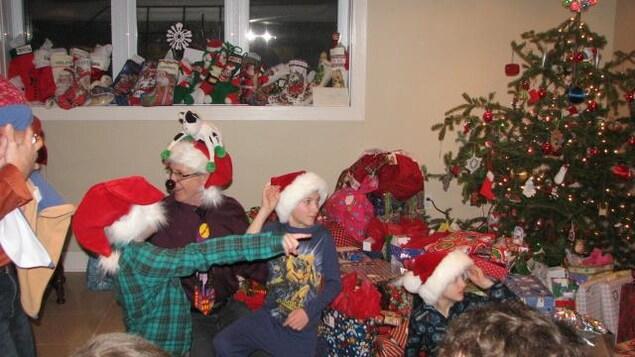 Claude Bélisle muni de son nez clignotant et de nombreux enfants autour d'un arbre de Noël.
