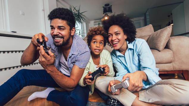 Un homme, une femme, et un enfant souriants jouent à un jeu vidéo.