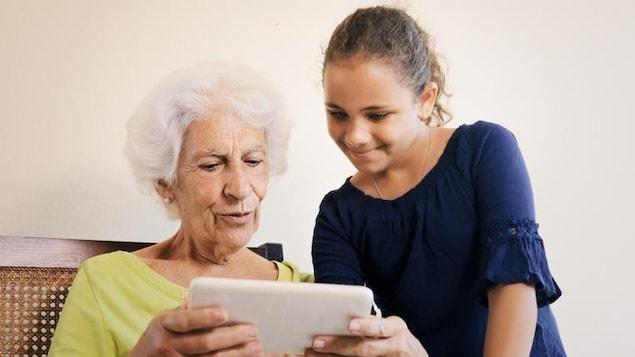 Une adolescente explique le fonctionnement d'une tablette à une aînée.