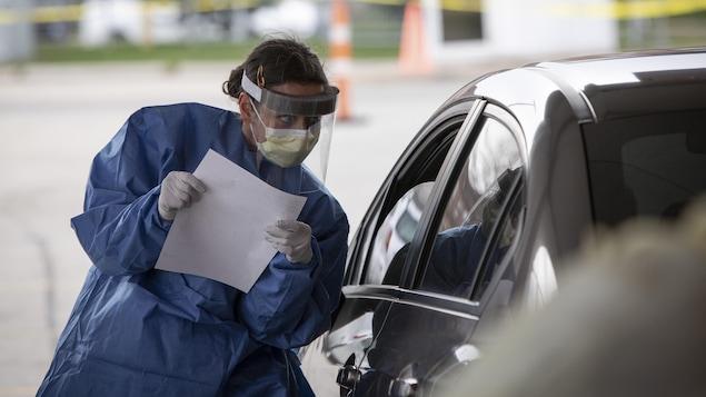 Une infirmière qui fait du dépistage à l'auto fait passer un questionnaire.