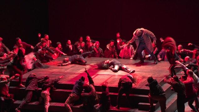 Une scène est éclairée en rouge, deux danseurs sont allongés, entourés par d'autres danseurs figurant une foule en colère.