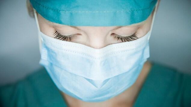 Une femme porte un masque et une tenue de soignant.