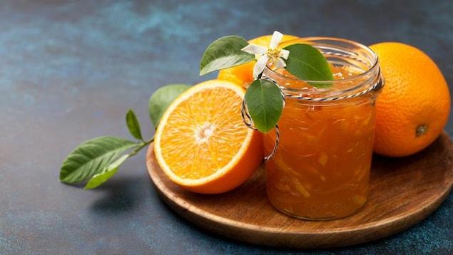 Un pot de marmelade entouré d'oranges.