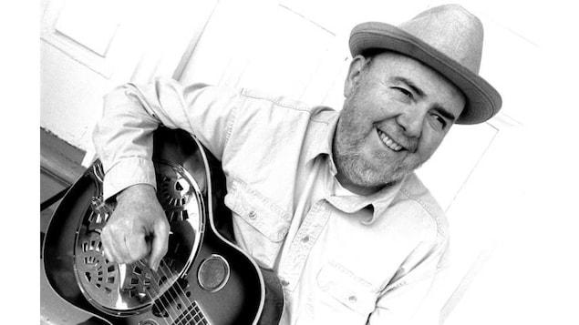 Portrait de Brian Blain, il porte un chapeau et joue de la guitare.