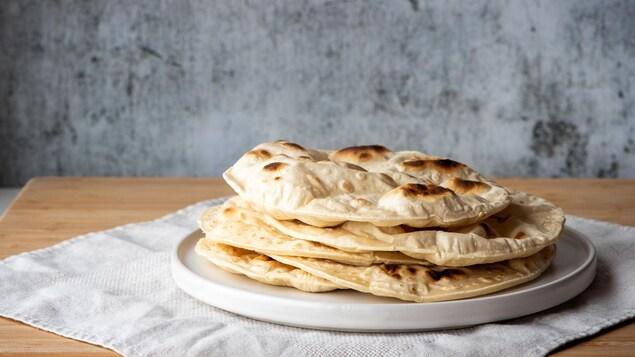 Des pains naan dans une assiette déposée sur un napperon blanc.