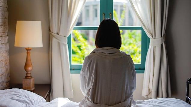 Une femme seule sur un lit, devant une fenêtre.