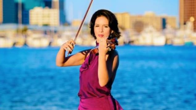 Tara-Louise est debout, porte une longue robe rouge et joue du violon devant le fleuve, on voit des immeubles flous sur l'autre rive.