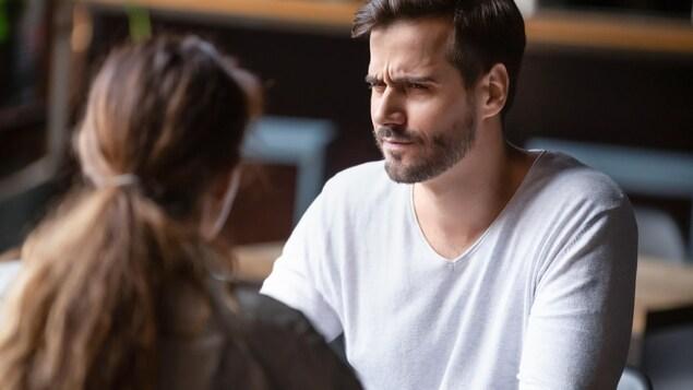 Un homme jete un regard dubitatif à la femme assise devant lui.