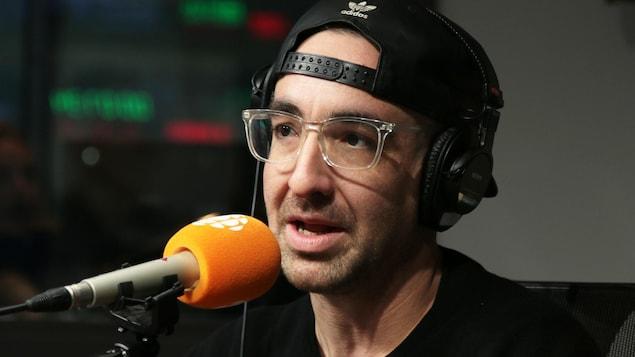 Un homme avec des lunettes de vue au cadre transparent et portant une casquette à l'envers parle au micro.