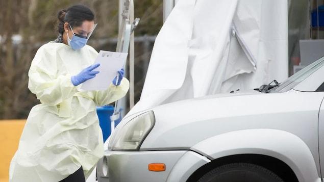 Une membre du personnel médical vêtue d'une jaquette et d'un masque lit un document devant une voiture à un centre de dépistage du coronavirus au volant.