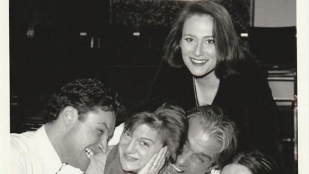 Cinq personnes posent pour une photo en se taquinant