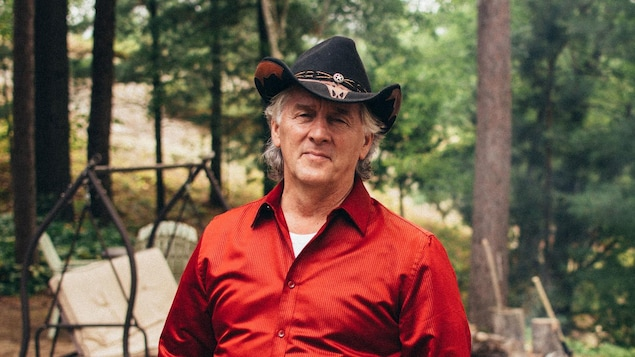 Un homme est debout dans la forêt. Il porte un chapeau de cowboy.