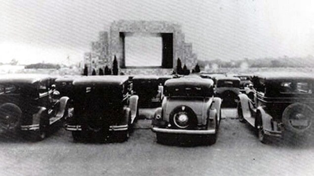 Photo en noir et blanc de voiture des années 1930 dans un ciné-parc.