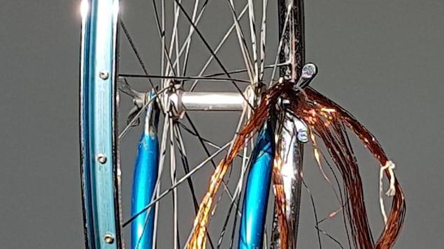 Une roue de bicyclette ornée de fils cuivrés.