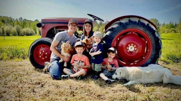 La famille devant un tracteur en compagnie de leur chien, un lapin, un cochon, une caille et un caneton.