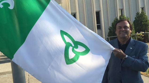 Donald Obonsawin avec le drapeau franco-ontarien à l'Université de Sudbury.