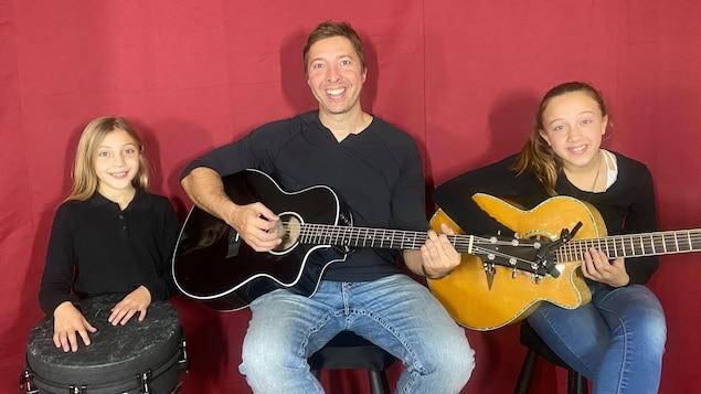 Un homme avec une guitare acoustique est entouré de ses deux filles, l'une avec un instrument à percussion et l'autre avec une seconde guitare acoustique