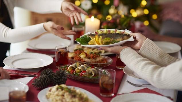 Des gens passent une assiette de poisson à une table bien garnie pour les Fêtes.