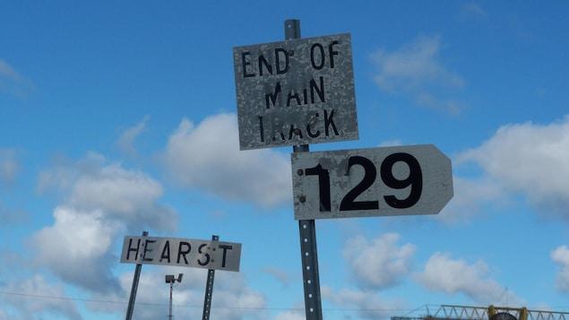 Trois panneaux de signalisations où sont inscrits, respectivement, « Hearst », « End of Main Track » et « 129 »