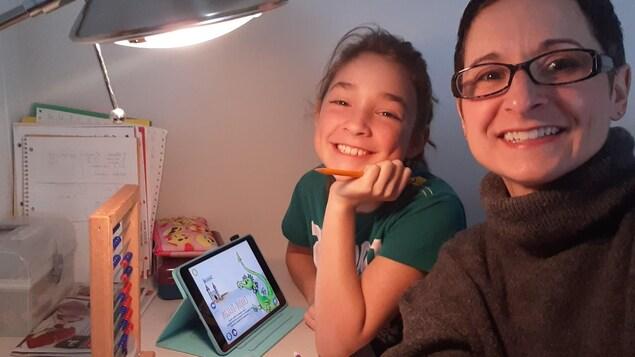 Une mère et sa jeune fille sont à la table avec du matériel électronique, du papier et des crayons.