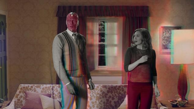 Un homme et une femme sont debout dans leur salon