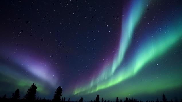 Une aurore boréale illumine le ciel d'une région éloignée.