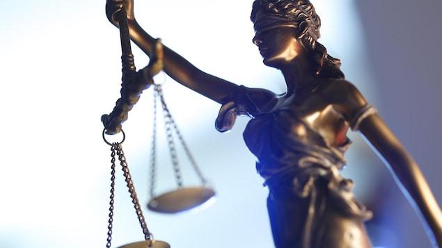 Une photo est prise d'une statue d'une balance, symbole de la justice.