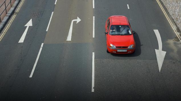Une personne conduit à gauche sur une route du Royaume-Uni.