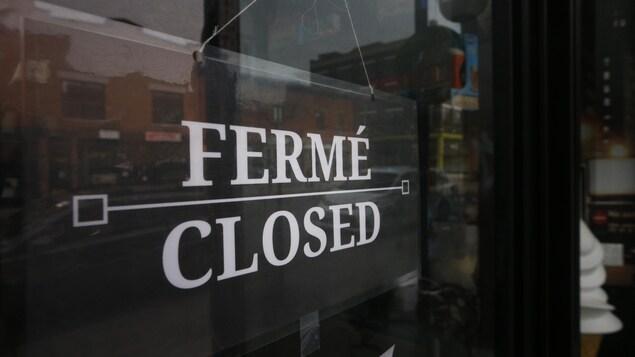 Un écriteau sur une porte indiquant que le commerce est fermé.