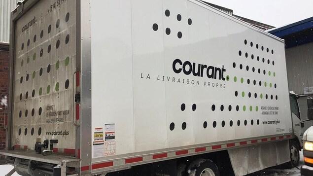 Un des camions électriques de Courant Plus est garé dans le stationnement de l'entreprise.