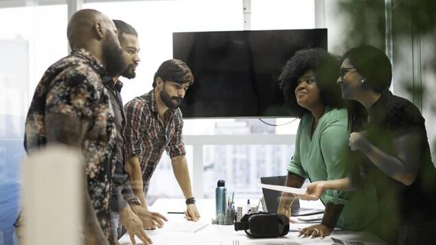 Des membres d'une équipe de publicitaires discutent autour d'une table.